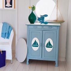 Meuble peint en bleu avec médaillon en contreplaqué et voiliers en balsa collés sur les portes