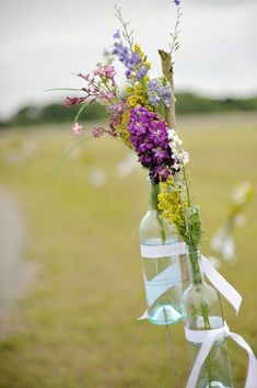 Wine glass bottles filled with wild flowers. A stunning aisle marker decor idea! {Danny K Photography}