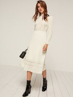 Come hither. This is a long sleeve, midi length dress with lace trim detail and a high neck.