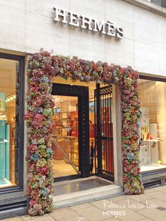 """Unlike most interior window displays this floral fixture is displayed on the exterior of the store, literally making it an """"outside of the box"""" display. The various hues of flowers pull colors from the window displays on each side, unifying the entire look of the store. The elegant floral arrangement compliments the luxurious branding of Hermes and ultimately attracts attention towards the store."""