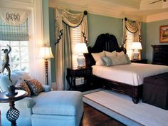 A designer found this heavily carved wood bed and created custom multi-layer window treatments. Wall paint, Benjamin Moore Wythe Blue, gives the room a regal feel and the custom-made trunk at the bottom of the bed was made to fit bed pillows for a tidy appearance.