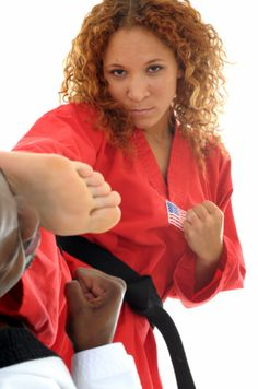 Martial artist executing a side kick to the head of her opponent.