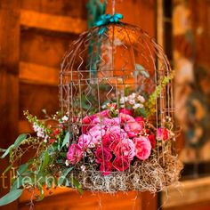 Vintage birdcage filled with pink flowers // Photography By Vanessa