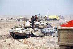 A British Challenger main battle tank waits by the Basra-Kuwait Highway near Kuwait City following the retreat of Iraqi forces during Operation Desert Storm. In the background are British armored personnel carriers and a wrecked garbage truck.