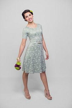 The Esther Dress is a trendy and modest knee length dress with grey-silver lace over a sage green liner.