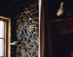 Shower Tiled with River Stones - in the bathroom, the shower is tiled in river stones found in Canada and mussel shells.