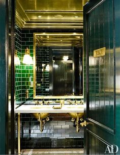 Gorgeous Ralph Lauren Polo Bar Bathroom. Peacock blue with green subway tile. Reflection and shine from lighting, large mirror and natural brass on ceiling and fixtures.