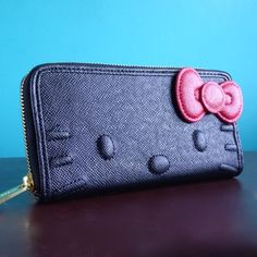 Sophisticated black wallet comes with wrap around zipper, red 3D bow, inside zipper pocket, ID window slot and 7 card slots. Faux leather material. One of Lulabites favorites! Dont forget the matching