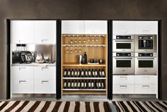 This recessed kitchen wall makes great use of a small space. Cabinets, preparation space, appliances, wine racks and glass storage are all i...