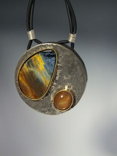 Sterling silver, 18k yellow gold, Pietersite and a star sunstone with rubber cord. Stasia Merritt
