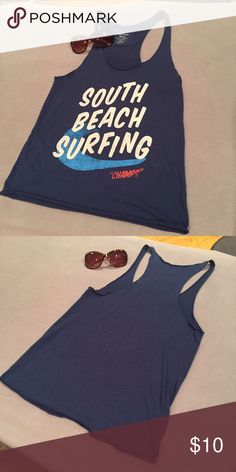 """Heritage 81 - forever 21 -racer back graphic tank. Heritage 82 Brand. Medium blue racer back tank. Size Medium fits like Small. """"South Beach Surfing Champs"""" in white letters with blue wave behind. Soft cotton fabric hits right at belt line. Heritage 1981 Tops Tank Tops"""