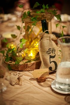 MY Table centre pieces. I created my own; down to painting the lanterns gold and cutting wood chunks. A look inspired by storybook woods with a rustic feel.    #wedding #candles #storybookwedding #lanterns #rustic #centrepieces