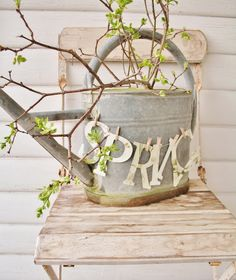 """tin watering can. """"spring"""" letters attached to string with mini clothing pins. greenery of choice to place in the can."""