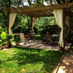 pergola with curtains tied to posts, elephant plant, shade trees