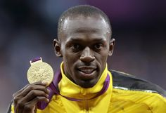 Usain Bolt poses with his gold medal for the men's 100-meters