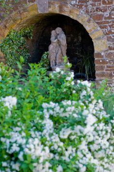 Garden sculpture of lovers placed under an ancient brick arch, private garden, Winchelsea, England