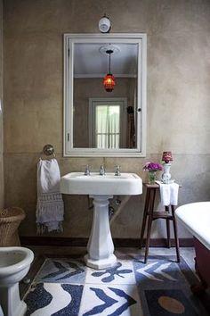 Baño rústico con piso de calcáreos y antigua bacha en una casa reciclada del Bajo San Isidro.