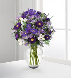 Purple irises are surrounded by lavender freesia, purple asters, and other soft accents.