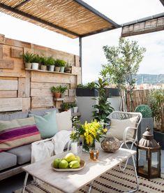 Terraza con sofá, butaca y mesa de centro, con panel de madera realizado con palés. #elmueble #terraza #palés #exterior #verano