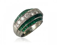 Platinum, emerald and diamond ring attributed to Oscar Heyman Brothers circa 1930. The ring is in a ridged form with the central band inset with round cut diamonds and the two lower steps to each side set with square cut emeralds.