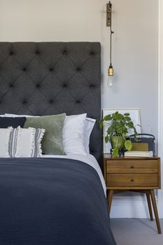 Interior Design by Imperfect Interiors at this Victorian terraced house in Balham, London. A palette of contemporary paint colours mixed with traditional period details- Paint & Paper Library Lead 5 on the walls, charcoal grey fabric headboard, mid-century bedside table & Buster & Punch brass wall lights make the master bedroom feel grown up and luxurious. Photo by Chris Snook