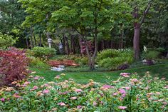 A low spot in the backyard was addressed by creating a planting area with a dry creek bed that promotes proper drainage. The entire property has been transformed into manicured woodlands, with an array of eye catching textures and colors.