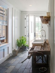 Back entry - antique workbench with modern fixtures for potting bench, double doors let in light