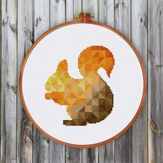 A cute squirrel cross stitch pattern is always a popular choice, and this geometric version offers a great twist. Made up in 24 gorgeous autumnal shades, it uses full cross stitches and three quarter stitches. We love how the varied shades give the impression the squirrel is enjoying a bit of sunshine. - Cross Stitch Collection magazine  PATTERN SPECIFICATIONS: Stitches: full cross stitch, three quarter stitch Floss: DMC stranded cotton Required Colors: 24 Stitches: 61 x 70  SUGGESTION…
