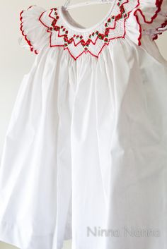 Little girl's summery white dress with red embroidered smocking...