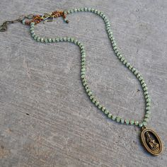 compassion - green crystal and African trade beads necklace with Quan Yin pendant from Love Pray Jewelry