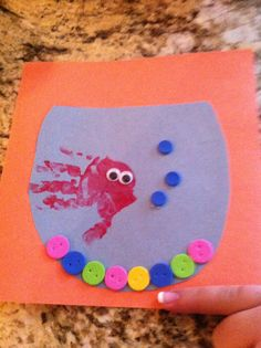 Finger painting fish bowl: orange and blue construction paper, foam stickers for bubbles and rocks, hand print, and googly  eyes! #fish #craft #fingerpaint #toddler #infant
