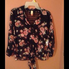Cute silk flowered top This is a No Boundaries size Lg 11-13 super cute silk top.  It is brand new never been worn.  It's black in color. The blouse has pink and white flowers, with attached leaves showing throughout.  This gives it a romantic and soft look.  The front can be tied as shown in the picture.  The sleeves can be worn long or you roll them up a half an inch or so and secure with the button and loop strip.  The front back shoulder panel is trimmed in lace, as part of the front…