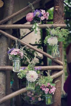 Flowers in jars hanging from wood  http://sarahannweddings.com/