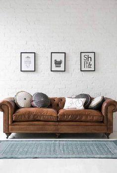sala com sofá marrom e almofadas redondas