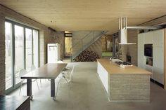 Der offene Wohnbereich mit Küche strahlt moderne Nüchternheit aus. Der dunkle Boden harmoniert mit den Lehmwänden und der Holzdecke.