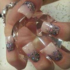 Beautiful flare tip acrylic nails polished with Innocence by China glaze accented with fame game glitter fade and a venique Polish faded slightly on top.