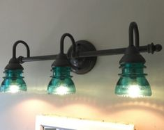 Real copper shades were repurposed with new UL listed electrical components and set with beautiful clear glass Hemingray insulators. Choose between clear and blue-green glass insulators. The fixture uses candelabra bulbs. 18 of black chain suspends the fixture from a dark bronze finished ceiling cap.