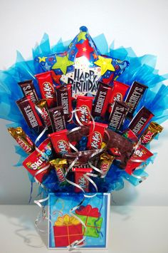 A handmade arrangement of your favorite candy in a birthday box with a birthday balloon. Arrangement contains a mixture of candy including Kit Kat, Skittles, Twix, Variety of M&Ms, Almond Joy, Snicker