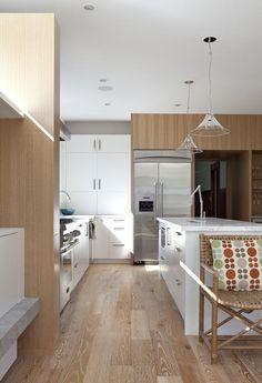 Remodelista, Medium Plenty, Oakland kitchen, view of white cabinets and stainless steel refrigerator, whitewashed oak flooring
