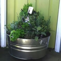 Herb pot made with three home depot tin tubs and buckets( Big tub about 20 dollars, med Bucket about nine dollars , Sm bucket I already had)(Drill hole in tubs to drain water)-For Herb Lables: chalk board (Spray Paint) silverware (29 cents each at goodwill)(tape off handle- only spray 4 coats on top of spoon or knife) Write on it with silver sharpie pen- permanent! Set of Wheel already put on wood about eight dollars by the pots at Home Depot.Top it of with a vintage playing card stuck in…