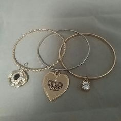 Set of 3 JUICY COUTURE Bracelets Gold Ton & Silver 3 Costume Jewelry Juicy Couture bracelets.  2 are gold tone - 1 has a large fake Diamond stone, 1 with black & fake diamond charm that open to put a small photo in. 1 is gold tone & has the signature Juicy Couture Heart on one side & a Crown on the other side.  All in excellent pre-loved condition. Juicy Couture Jewelry Bracelets