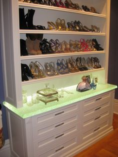 """The LED underlit countertop in this walk-in closet matches the Swarovski hardware to create a perfect display for your """"footwear art""""."""