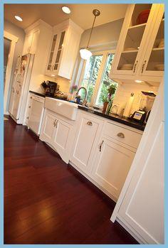 kitchen, black counters white cabinets, farm sink, school house light fixture.