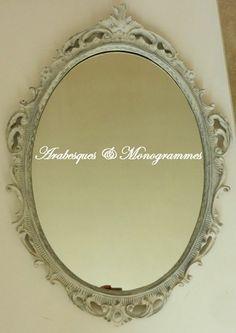 Beau miroir ovale en bois (anciennement doré) à décor de fleurs et de volutes stylisées, qui rappelle le style Rocaille français. Une première couche de fond taupe mat a ét - 17114110