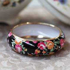 "Dancing Flowers Floral Bangle 16.99 at shopruche.com. Fun and playful floral bangle with pink, yellow, and white flowers with green leaves on a black background.  Width: 1"" Diameter: 2.75"""