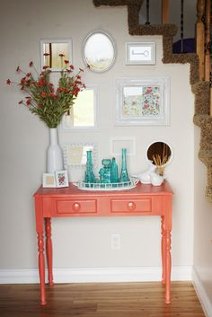 Love this entryway!  Scrapbook paper in frames, tall flowers, coral table.