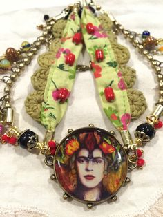Frida collage artwork set in a bezel and encased in resin.  ©Andrea Matus deMeng #artisanjewelry #assemblagejewerly