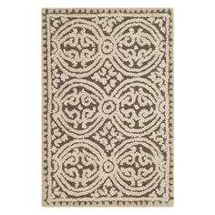 Elegantly anchor your parlor or dining room with this hand-tufted wool rug, showcasing an eye-catching circle medallion motif in brown.
