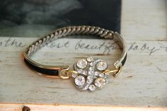 Assemblage bracelet created with vintage rhinestone button attached to vintage stretch watch bracelet