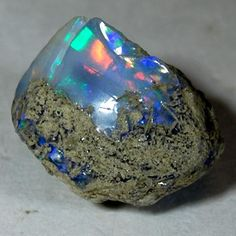Opal Gemstone meaning    Opal was formed many millions of years ago, when a combination of silica and water flowed into cracks and spaces in the ground. This then gradually hardened and solidified to become opal. Opals contain water, which makes them very sensitive to heat. They are soft and can be cracked or chipped easily. Opals should be stored in moist absorbent cotton.
